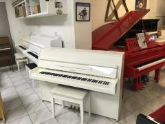 Bílé pianino Yamaha se zárukou.