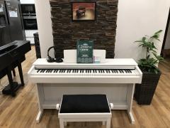 Bílé digitální pianino YAMAHA včetně židle a sluchátek.