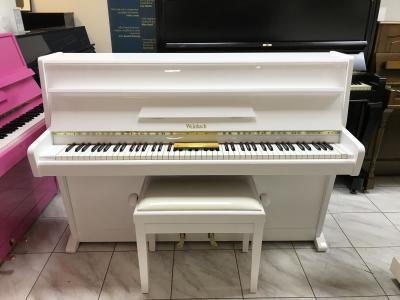 Menší bílé pianino.