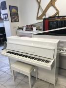 Menší bílé pianino Petrof s židlí.